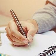 Estudiante escribiendo apuntes en clase